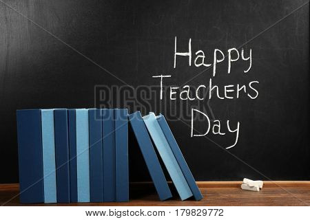 Books on blackboard background. Happy Teacher's Day concept