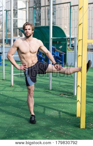 Athletic Bearded Man With Muscular Body Stretching On Outdoor Stadium