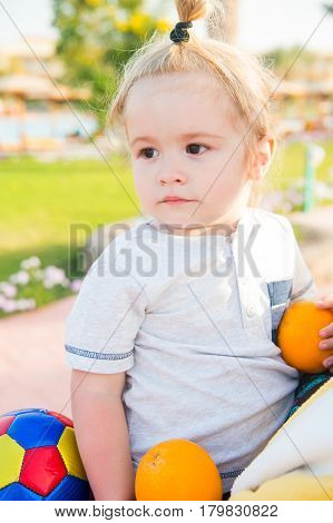 Small Baby Boy With Colorful Ball And Orange Fruit