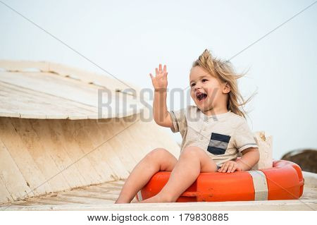 Small Happy Baby Boy Sitting In Red Lifeline Or Lifebuoy