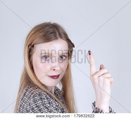 Young woman raising index finger making a point