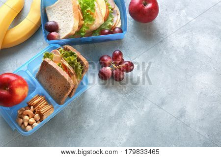 Lunchboxes with sandwiches and different products on grey background