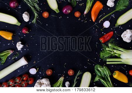 Selection of healthy vegetables and spices, veggie frame, black background. Top view, copy space.