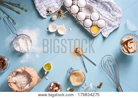 Bakery ingredients - flour, eggs, butter, sugar, yolk, almond nuts on blue table. Sweet pastry baking concept. Flat lay, copy space, top view.
