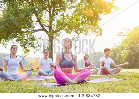 Meditation in yoga group in summer in the nature