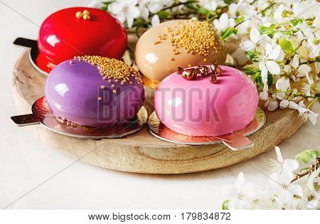 Fashionable mousse cake with a mirror glaze decorated with spring flowers. Light white background