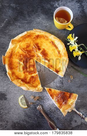 French cheese flan and daffodils on dark background. Top view