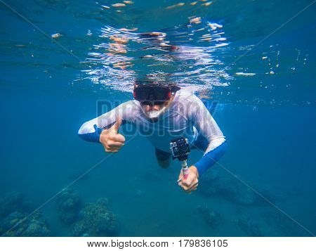 Young sportsman in snorkeling mask shows thumb underwater. Snorkel in tropical lagoon undersea photo. Summer holiday activity. Water sport in open sea. Exploring tropical coral reef. Man on vacation