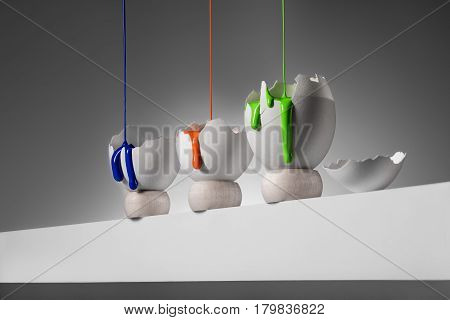 Three colorful stains of paint  seep into the broken eggs on a gray background
