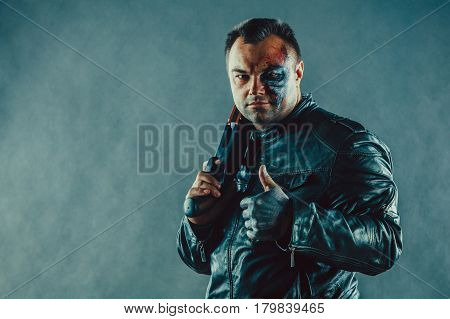 Dangerous Man With Scares And Burns On The Face Is Holding A Shotgun.