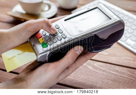 Payment by credit card in cafe with terminal and keyboard on wooden desk background