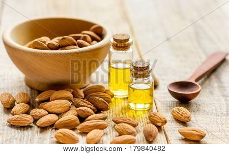 natural cosmetic set with almond oil and bowl of almonds on brown wooden table background
