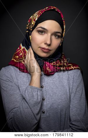Fashion model wearing hijab for conservative modern clothing mostly associated with muslims middle eastern and east european culture. The outfit depicts the traditional headscarf in vogue style.