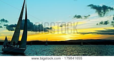 Sailing yacht in silhouette with golden sunset and water reflections. Photo captured in Lake Macquarie New South Wales Australia.