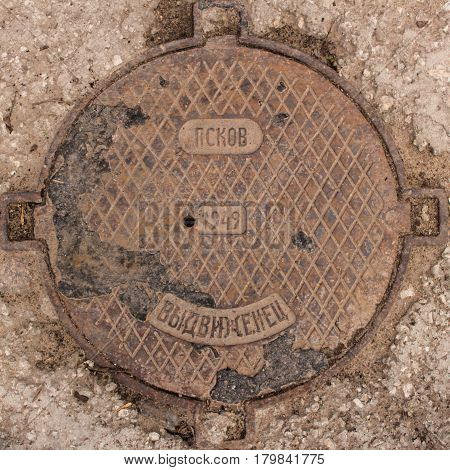 Old rusty cast-iron hatch-cover with inscriptions in Russian. Inscriptions from the top down read: