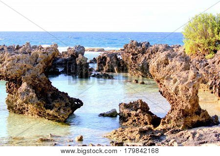 Rock formations, Rota Rock formations jutting out of the shoreline form a cove in Rota, Northern Mariana Islands.