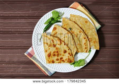Healthy Indian Mooli or Radish paratha or stuffed flatbread with coriander and green chilies on wooden background with copy space.