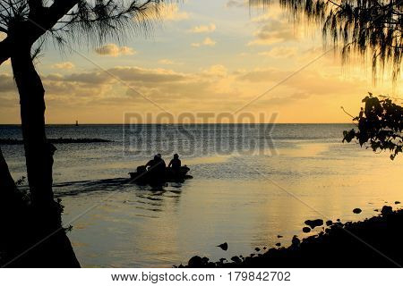Boaters at the Fishing Base Three men went out on a boat to go fishing at sunset in Saipan, Northern Mariana Islands