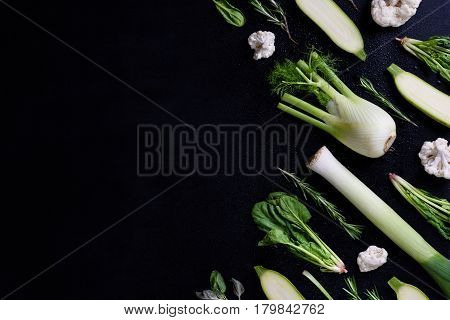Green vegetables over black background,knolling style. High angle view, copy space.