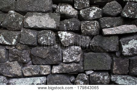 Grey stone wall background or wallpaper. Rough grey stone bricks design. Masonry wall made of big rocks. Rustic stones texture. Stone brickwork photo. Solid protection safety or durability concept