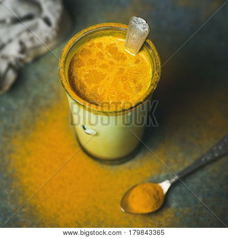 Golden milk with turmeric powder in glass over dark background, copy space, square crop. Health and energy boosting, flu remedy, natural cold fighting drink. Clean eating, weight loss concept