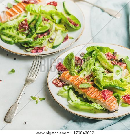 Healthy energy boosting spring salad with grilled salmon, blood orange, olives and quinoa over grey marble background, selective focus, square crop. Clean eating, dieting, detox, weight loss concept