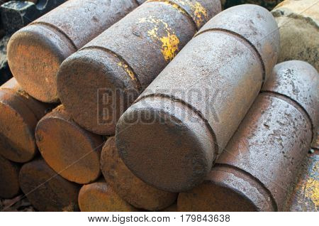 Medieval bombs with patina. Iron shell of cannon balls. Historical military ammunition. Unused cannon balls pile. Stack of rustic cannon shells. Military object. Unexploding war missile of XIX century