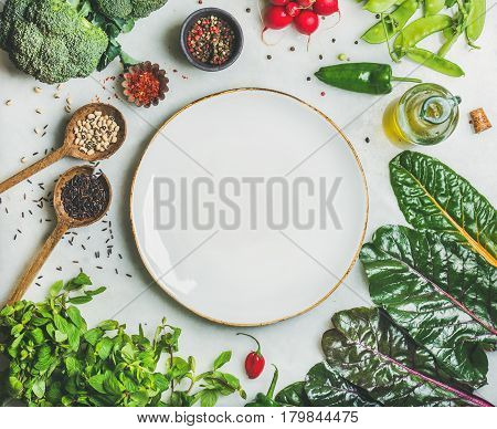 Fresh raw greens, vegetables and grains over light grey marble kitchen countertop, wtite ceramic plate in center, top view, copy space. Healthy, clean eating, vegan, detox, dieting food concept