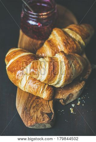 Breakfast concept. Freshly baked croissants with raspberry jam in jar on rustic wooden board over dark background, selective focus
