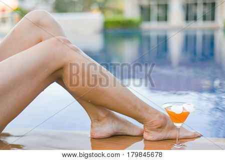 Women relaxing near luxury swimming pool,Beautiful woman legs sunbathing near swimming pool.