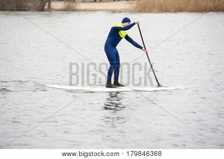 athletic man in a diving suit stand up paddle board on the river in the city