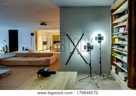 Modern flat with glowing lamps and a parquet with a carpet on the floor. There is a kitchen zone with table and stools, sofa, wooden table with a vise, decorations on the wall, shelves with books.