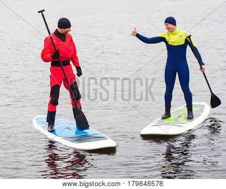 two athletic man in a diving suit stand up paddle board on the river in the city