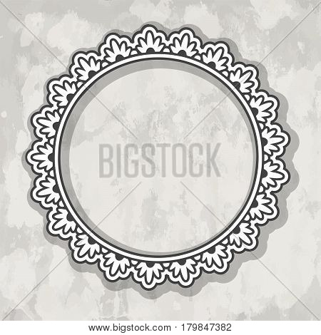 One round ornate paper cut frame over grey textured background.