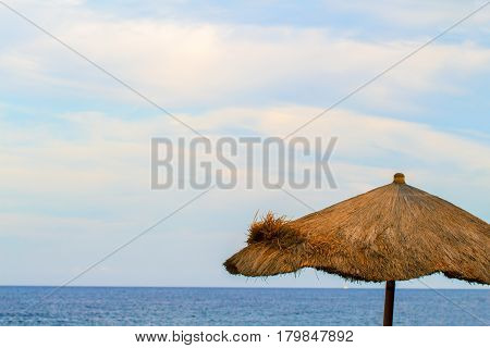 Palm leaves umbrella and sea. Peaceful landscape of tropical island resort. Marine view minimal photo background. Caribbean or Hawaii vacation banner template. Dry grass beach umbrella and seashore