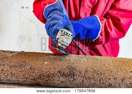 Grinding machine works and sparking by man in workshop wearing safety helmet and gloves