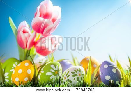 Easter eggs hiding in the grass with tulips. Studio shot