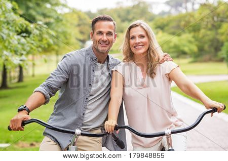 Mature couple riding bikes at park in a summer day. Smiling senior couple enjoying the ride on bicycle in park. Portrait of a couple on vacation relaxing on a bicycle and looking at camera.