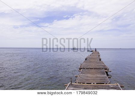 Blue sea with ship and wooden pier landscape. Romantic seaside view toned photo. Rustic timber pierce in still sea. Summer holiday seascape trendy banner template with text place. Seashore background