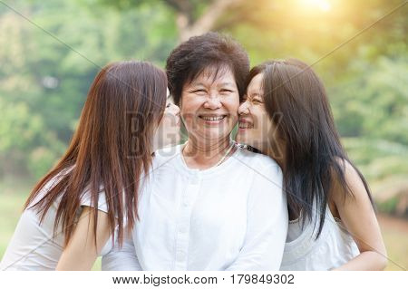 Portrait of beautiful Asian daughters kissing elderly mother, senior adult woman and grown child. Outdoors family at nature park with beautiful sun flare.