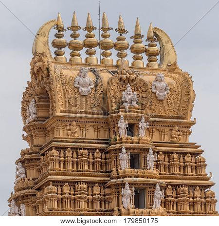 Nanjangud India - October 26 2013: Focus on top and the elaborately decorated Kalasam of the main Gopuram of Sri Srikanteshware temple in Ganjangud Karnataka State. Golden decoration white statues.