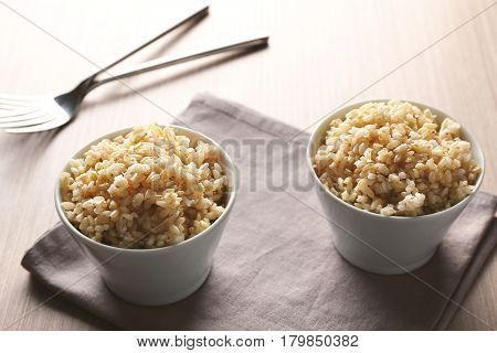 Two bowls of brown rice on napkin