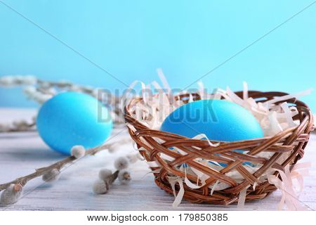 Easter eggs and bowl on white wooden table