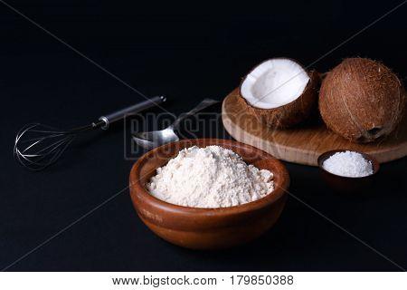 Coconut flour in wooden bowl on dark background