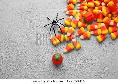 Tasty Halloween candies on light background
