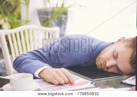 Businessman heavy workload sleep at office desk with finance sheet calculator and coffee. concept for overworked