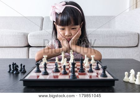 Tired Asian Chinese Little Girl Playing Chess At Home