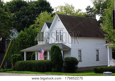 HARBOR SPRINGS, MICHIGAN / UNITED STATES - AUGUST 4, 2016: A single family Victorian home flies the American flag on West Third Street near downtown Harbor Springs.