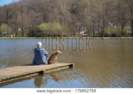 Man sitting with his dog on landing stage at nature lake