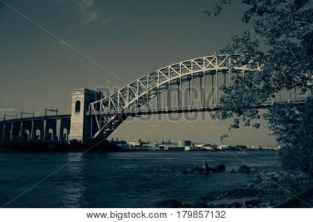 The Hell Gate Bridge and the trees in vintage style at Astoria Park, New York